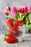 Goblet of fresh strawberries and bouquet of pink tulip Stock Photography