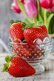 Goblet of fresh strawberries and bouquet of pink tulips Stock Image