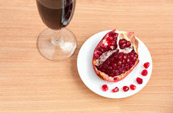 Goblet of wine and a pomegranate on the table Stock Photos