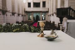 Goblet of wine on table during a wedding ceremony nuptial mass. Religion concept. Catholic eucharist ornaments for the celebration. Of the Eucharist stock photo