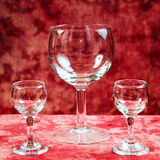Goblets. Two small and one large glass goblets are empty against a red background Royalty Free Stock Photography