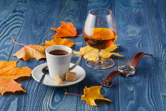 Goblets of brandy and cup of hot coffeeon wooden old counter top Royalty Free Stock Photo