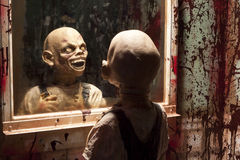 Goblin in Mirror. Scary monster ghoul looking at himself in the mirror of a bloody bathroom Stock Image