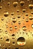 Gocce ambrate dorate dell'acqua Fotografia Stock Libera da Diritti