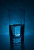 Gocce dell'acqua che versano nel vetro Immagine Stock Libera da Diritti