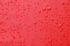Gocce dell'acqua su colore rosso Fotografia Stock Libera da Diritti
