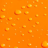 Gocce dell'acqua sul Ba arancione del metallo Fotografia Stock