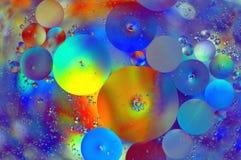 Gocce dell'olio su acqua immagine stock