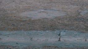 Gocce della caduta della pioggia alla pavimentazione che forma una pozza Lasso di tempo stock footage