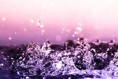Gocce della macro del primo piano dell'acqua con una caduta di luce solare sulla superficie pesante dell'acqua della spruzzata su fotografia stock