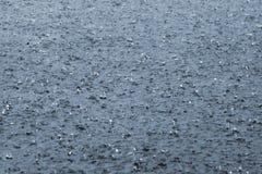 Gocce della pioggia su un lago Immagini Stock