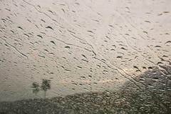 Gocce della pioggia sul vetro di finestra Davanti ad un paesaggio nuvoloso Fotografie Stock