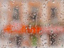 Gocce della pioggia sulla finestra di vetro Il paesaggio urbano fuori della finestra in una sfuocatura L'effetto del bokeh Fotografia Stock