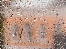 Gocce della pioggia sulla finestra di vetro Il paesaggio urbano fuori della finestra in una sfuocatura L'effetto del bokeh Fotografia Stock Libera da Diritti