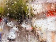 Gocce della pioggia sulla finestra di vetro Il paesaggio urbano fuori della finestra in una sfuocatura L'effetto del bokeh Immagine Stock
