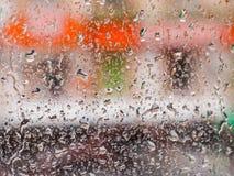 Gocce della pioggia sulla finestra di vetro Il paesaggio urbano fuori della finestra in una sfuocatura L'effetto del bokeh Immagine Stock Libera da Diritti