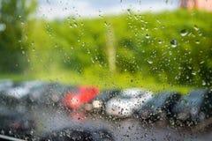 Gocce della pioggia sulla finestra Una fila delle automobili confuse fuori della finestra Pioggia di estate un giorno soleggiato Fotografia Stock Libera da Diritti