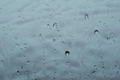 Gocce di acqua che cadono sul vetro del ` s della finestra fotografie stock libere da diritti