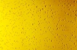 Gocce di acqua di struttura sul primo piano giallo della bottiglia come fondo Fotografia Stock Libera da Diritti