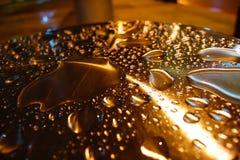 Gocce di acqua illuminate sulla colonna del metallo Fotografie Stock