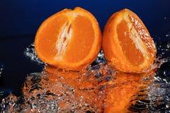 Gocce di acqua intorno al mandarino sullo specchio blu del fondo Fotografie Stock Libere da Diritti