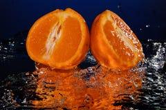 Gocce di acqua intorno al mandarino sullo specchio blu del fondo Fotografia Stock Libera da Diritti