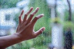Gocce di acqua su un vetro e su una mano fotografie stock