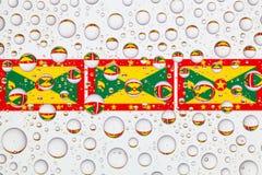 Gocce di acqua su vetro e sulle bandiere della Granada Fotografia Stock Libera da Diritti