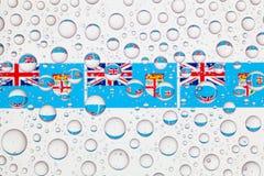 Gocce di acqua su vetro e sulle bandiere delle Figi Fotografia Stock