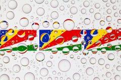 Gocce di acqua su vetro e sulle bandiere delle Seychelles fotografia stock
