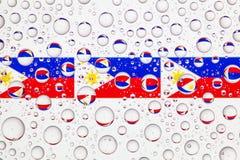 Gocce di acqua su vetro e sulle bandiere di Filippine Immagine Stock