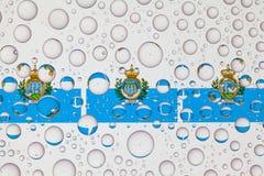 Gocce di acqua su vetro e sulle bandiere di San Marino fotografie stock libere da diritti