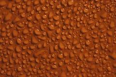 Gocce di acqua sul fondo arancio di colore Immagine Stock