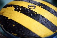 Gocce di acqua sulla barra d'attracco gialla nera sfuocatura Struttura Fondo fotografie stock libere da diritti