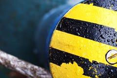 Gocce di acqua sulla barra d'attracco gialla nera sfuocatura Struttura Fondo immagini stock libere da diritti