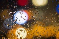 Gocce di acqua sulla finestra con il fondo di colore Immagine Stock