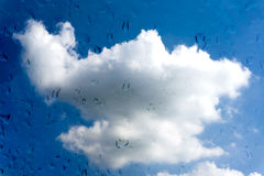 Gocce di acqua sulla finestra di vetro sopra cielo blu Fotografia Stock Libera da Diritti