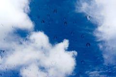 Gocce di acqua sulla finestra di vetro sopra cielo blu Fotografia Stock