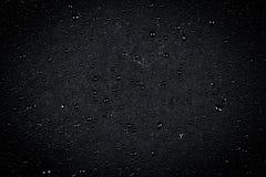 Gocce di acqua sulla pietra scura immagini stock