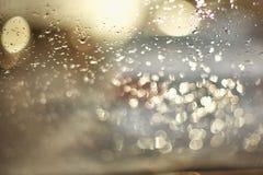 Gocce di acqua sulla superficie del vetro durante il tramonto Nella foto c'è abbagliamento dagli oggetti, la foto è da immagini stock