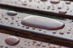 Gocce di acqua sulle plance di legno della tavola Fotografia Stock