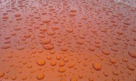 Gocce di pioggia arancio bruciate Fotografie Stock