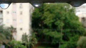 Gocce di pioggia blu sopra una finestra aperta immagine stock