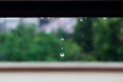 Gocce di pioggia che gocciolano su una finestra Fotografia Stock