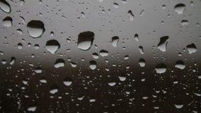 Gocce di pioggia d'argento su vetro, primo piano Immagine Stock