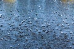 Gocce di pioggia della pioggia che volano e che si schiantano sull'asfalto immagini stock libere da diritti