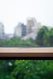 Gocce di pioggia ed acqua che versano su una finestra immagine stock