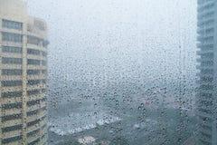 Gocce di pioggia in finestra con paesaggio urbano Immagini Stock
