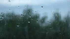 Gocce di pioggia fresche che provano rottura nell'appartamento soffocante attraverso i vetri di finestra sporchi video d archivio