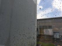 Gocce di pioggia, gocce di acqua di pioggia su un vetro di finestra con costruzione vaga e strada fotografia stock